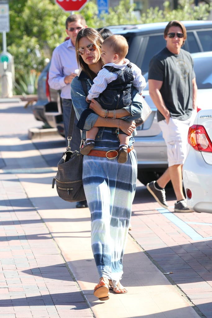 Alessandra Ambrosio wore a tie-dyed Lily Aldridge for Velvet maxi dress with a denim jacket, a tan belt, mirrored aviators, and her gray Givenchy bag while hanging with her family in Malibu.