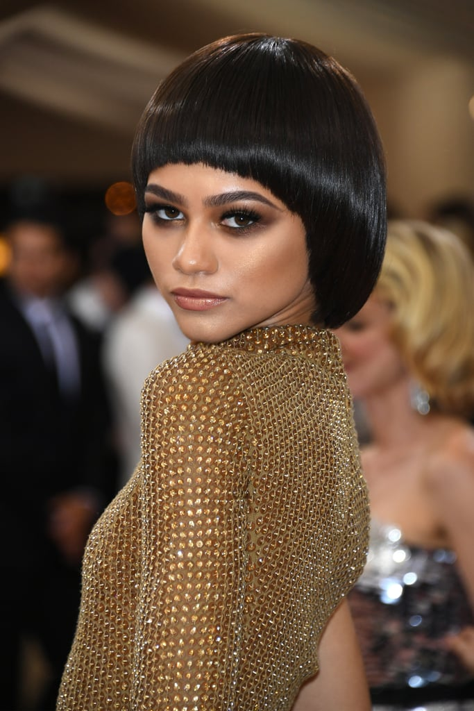 Zendaya loves to rock unique hairstyles, and she didn't stop at the Met Gala. The triple threat sauntered down the red carpet in a gold Michael Kors gown and a bowl-cut wig (we've seen it before but not in a while). The retro wig drew just the right amount of attention to her bronzed eyes.  While Zendaya often does her own makeup for award shows, we aren't certain if she's responsible for her Met Gala look. We can say that her copper eye shadow is sprinkled with gold flecks. It's smudged under her eyes, casting a sultry shadow. Once again, we're fully impressed by Zendaya's personal beauty flare.