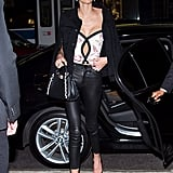 Kaia is wearing a Hudson denim jacket and leather pants. She paired her look with a cutout printed blouse, Christian Louboutin heels, and a Fendi bag.