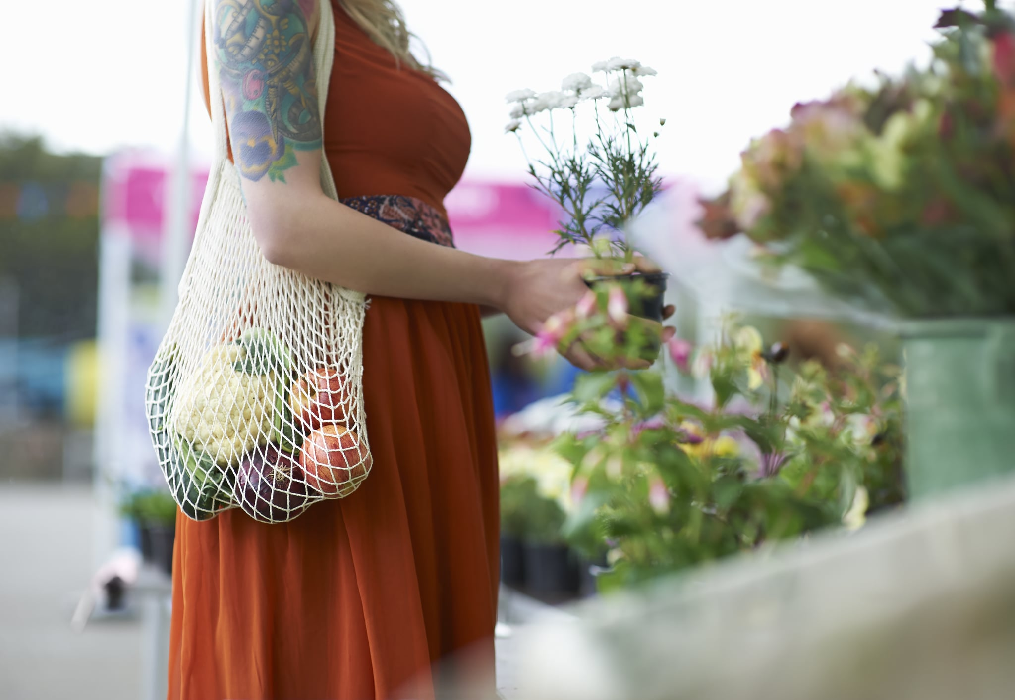 A woman with tattoos shopping on a local market picks up a potted flower plant and carries fresh groceries in her plastic free reusable bag.