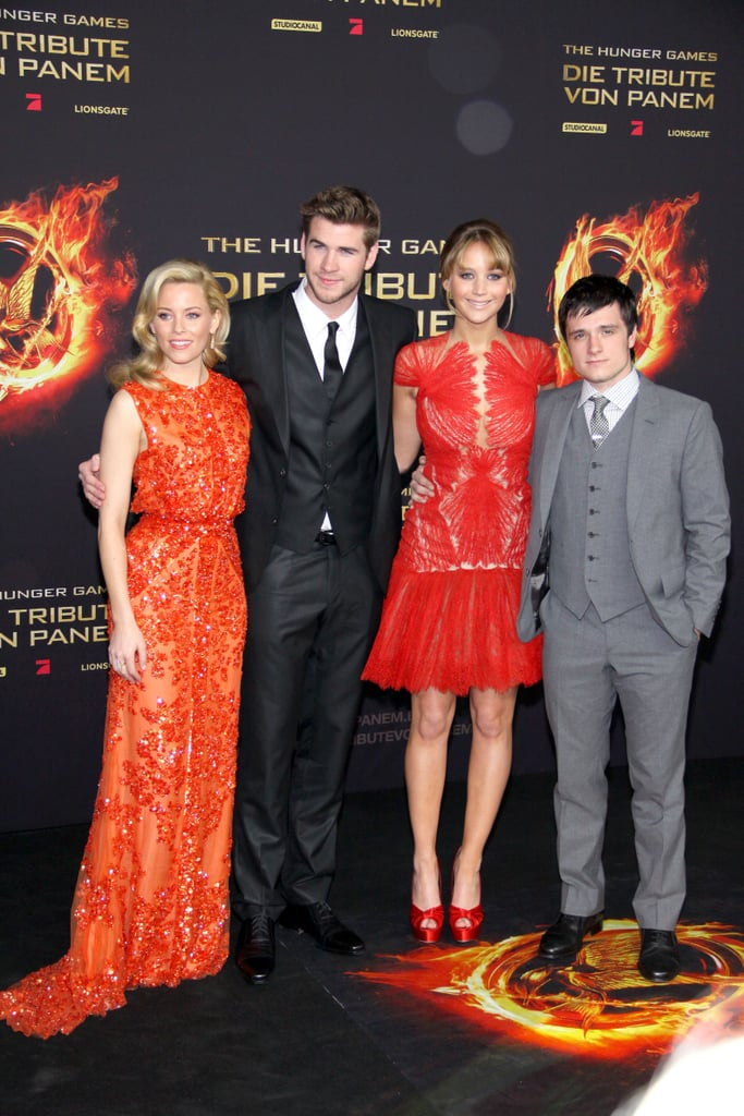 "The Hunger Games rolled into Berlin today for the film's latest premiere. Jennifer Lawrence and Elizabeth Banks arrived in fiery hues while Liam Hemsworth and Josh Hutcherson stuck with traditional dark suits. Germany marks the third stop on the European leg of their international press tour following layovers earlier this week in Paris and London.  Elizabeth picked a bright Elie Saab for today's event while Jennifer switched up her look by choosing a short red Marchesa, which showed off her fit legs. Her legs and arms were a hot topic recently while chatting with press about her action scenes. Jennifer describes her running in the film as ""unfortunate"" due to her ""karate hands."" We talked with her condtioning coach and got the behind-the-scenes secrets to achieving Katniss's form — stay tuned for more on how to run like Jennifer and how she got in shape for the role of a lifetime."