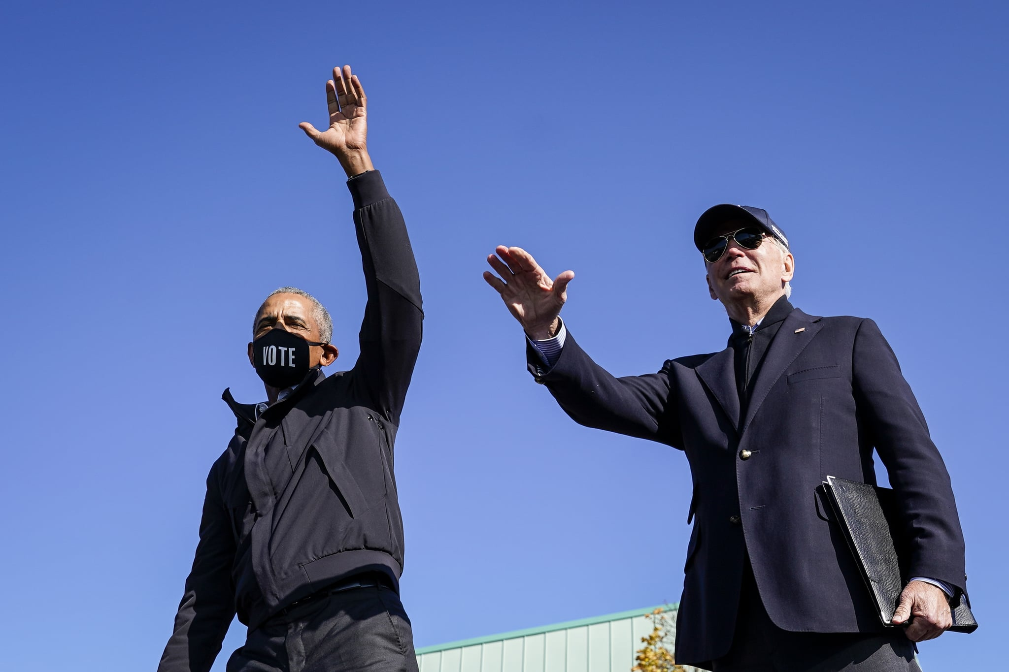 FLINT, MI - OCTOBER 31: Former U.S. President Barack Obama and Democratic presidential nominee Joe Biden wave to the crowd at the end of a drive-in campaign rally at Northwestern High School on October 31, 2020 in Flint, Michigan. Biden is campaigning with former President Obama on Saturday in Michigan, a battleground state that President Donald Trump narrowly won in 2016. (Photo by Drew Angerer/Getty Images)
