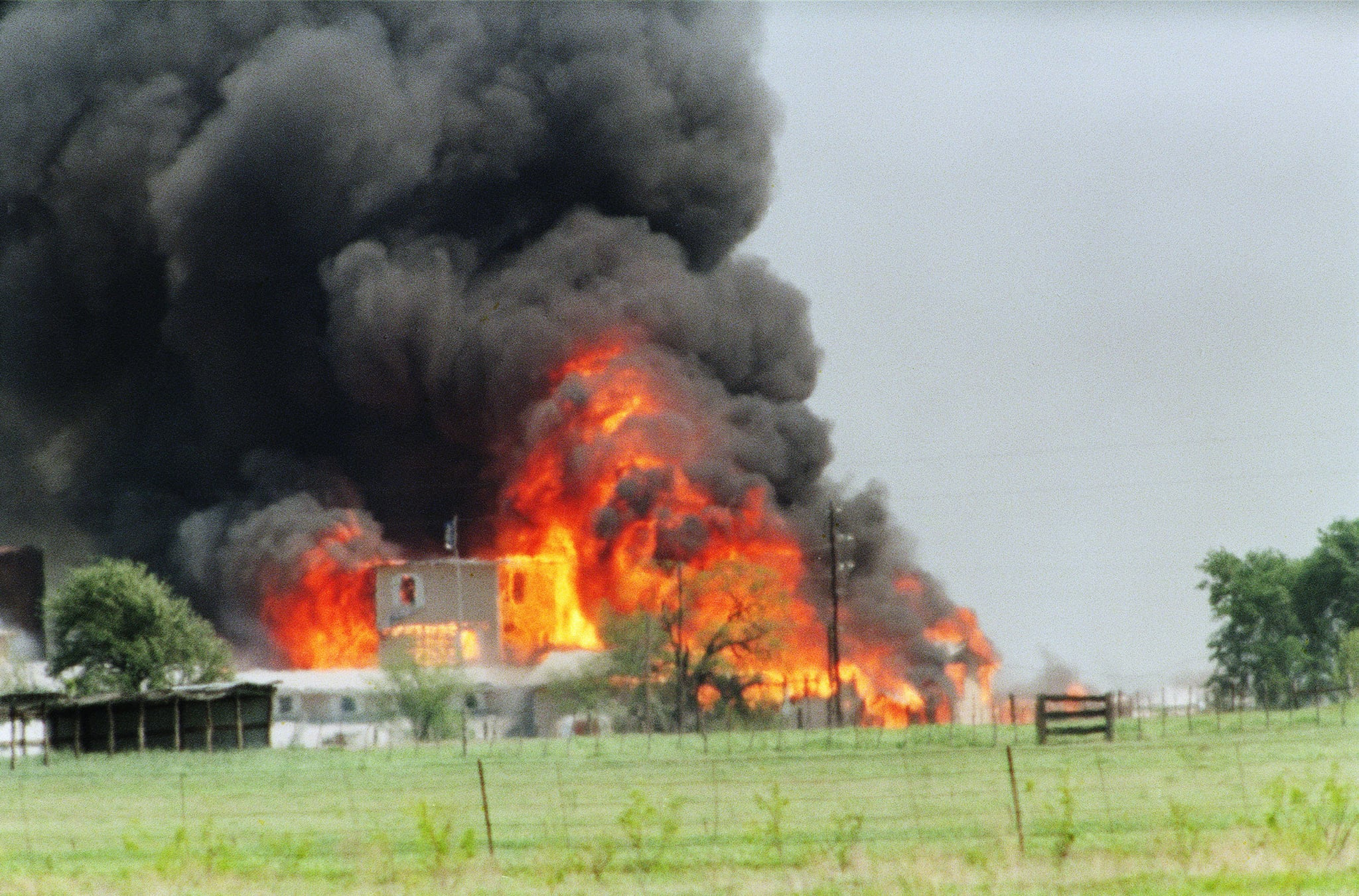 The Branch Davidian cult compound observation tower in Waco, TX is engulfed in flames after a fire burns the complex to the ground 19 April 1993. (Photo by TIM ROBERTS / AFP) (Photo by TIM ROBERTS/AFP via Getty Images)