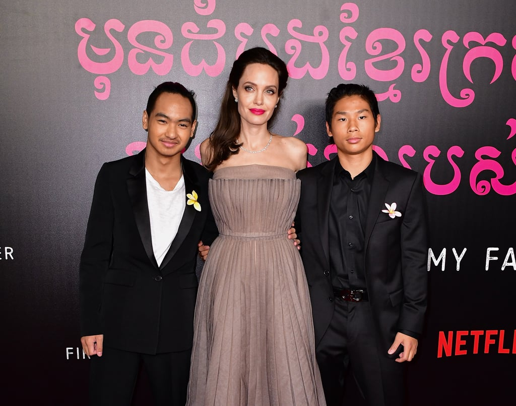 Angelina Jolie and her children have been stepping out a lot lately, and we can't get enough. After taking the Toronto International Film Festival by storm, the big, happy family attended the NYC premiere of Angelina's movie, First They Killed My Father, on Thursday night. The actress and her six children put on a united front as they all incorporated what appears to be plumeria flowers into their outfits, which symbolize positivity. Of course, it was her eldest sons Maddox and Pax, who helped work on the film, that really stole the spotlight as they sweetly escorted their mom down the red carpet. Seriously, she looks so proud!  Angelina's two eldest sons also weren't the only men in her life that showed their support. Her father, Jon Voight, who had previously been estranged from her for nearly seven years, made a cameo at the event. The two ended their longtime feud in 2010, when Brad Pitt convinced them to make a mends. Even though the father-daughter duo didn't pose for pictures together, the actor was all smiles as he posed with his brother, Angelina's uncle, Chip Taylor.