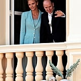Princess Charlene of Monaco and Prince Albert II of Monaco look out from the balcony.