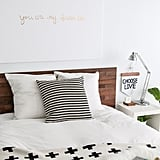 A simple Ikea headboard is elevated with the application of wood planks.