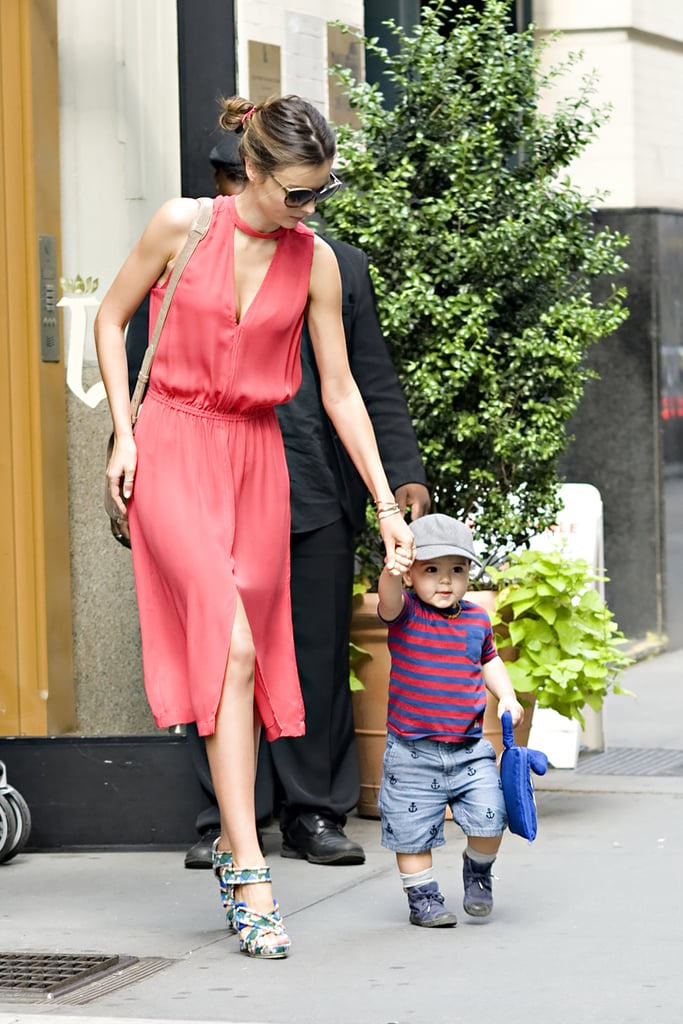 Miranda Kerr guided her 18-month-old son Flynn Bloom from their NYC apartment to a waiting car yesterday. The Victoria's Secret model, who was effortlessly stylish in a bright dress and printed heels, held hands with Flynn, who dressed in a sailor-inspired outfit. He was also carrying his own fabric activity book, My Quiet Book! Flynn's dad Orlando Bloom wasn't with them on this occasion as he's working in London. She has also been occupied with sexy photo shoots. This month Orlando and Miranda celebrate their two-year wedding anniversary.