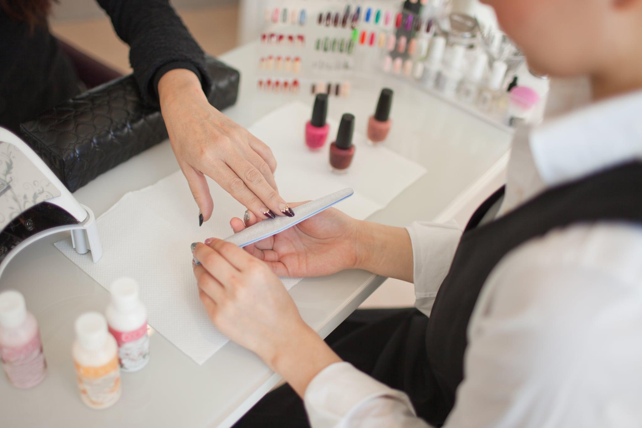 Manicurist polishing finger nails at beauty salon, Harajuku, Tokyo, Japan.