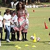 During her and William's April 2016 trip to India, Kate joined a group of children to play ball games — in heels!
