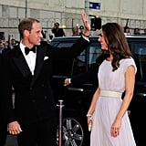 Kate checks out Prince William as he waves to fans at the BAFTA event.