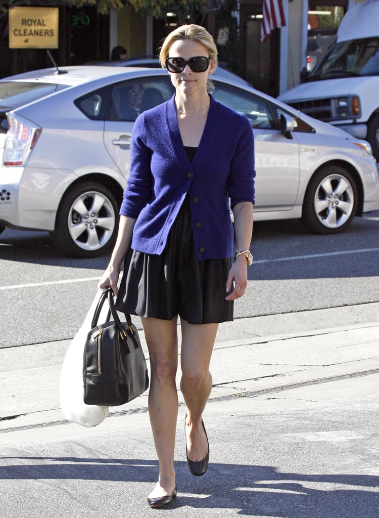 Reese was snapped taking a stroll in a simple black dress, a cardigan, and comfy flats.