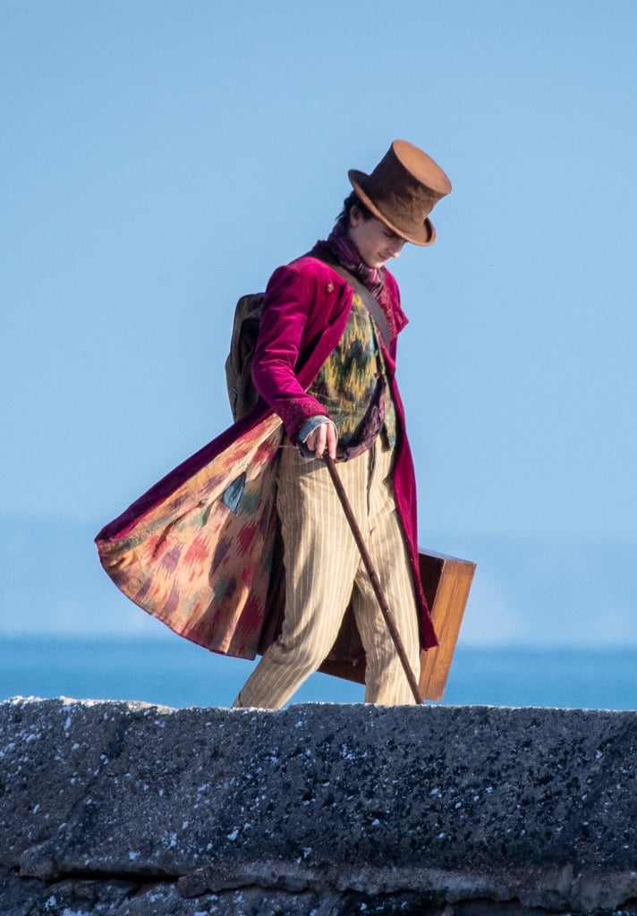 Shoutout to the breeze in England for revealing the colourful underside of Timothée's Wonka coat. As for the layers underneath, he's rocking a pink and purple patterned scarf tucked into a black and mustard button-up waistcoat.