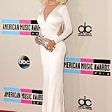 Christina Aguilera oozed retro glamour in a long-sleeved white Maria Lucia Hohan dress with strategically placed cut-outs, a sparkling box clutch, Lorraine Schwartz flower rings, and peep-toe Jimmy Choo pumps.