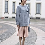A sweater, a skirt, and flats