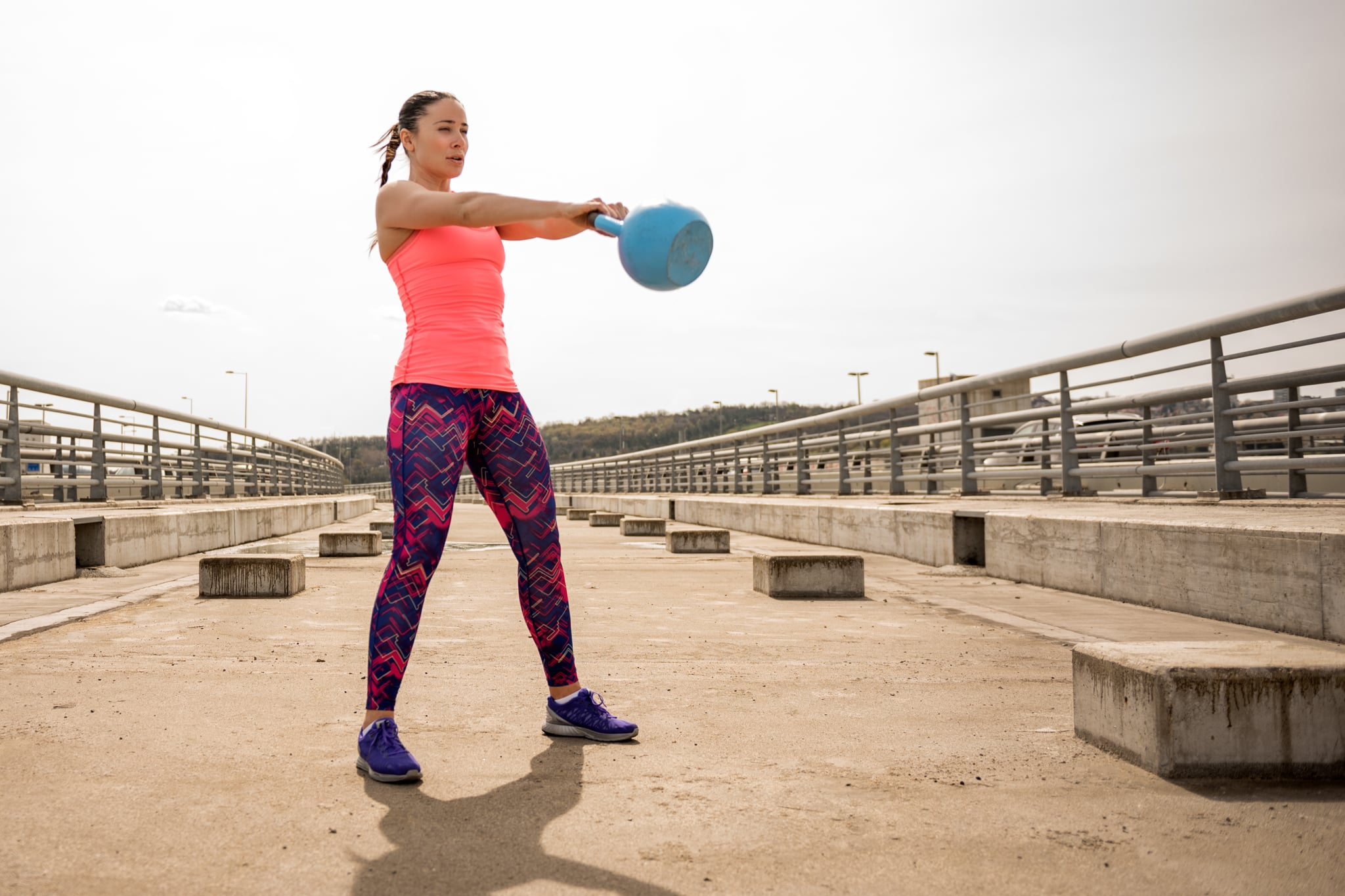 Woman exercising kettlebell swings.