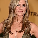 Jennifer Aniston's Amrit body chain highlighted her plunging neckline, and her Fred Leighton earrings added extra warmth to her look.