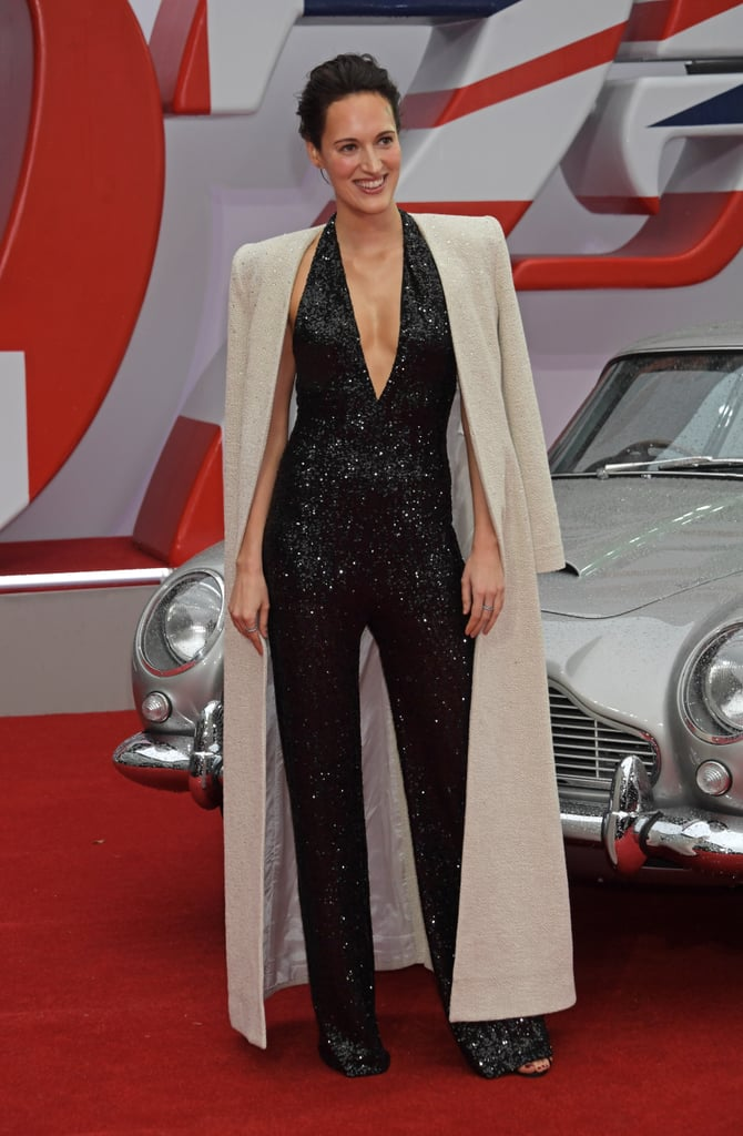 For the first time since January, Phoebe Waller-Bridge has returned to the red carpet, and the wait was worth it. Phoebe arrived at the No Time to Die premiere in London draped in a sleeveless Azzaro jumpsuit coated in enough black sequins to mirror all the stars in the sky on the nights we've spent dreaming of Fleabag's nonexistent third season. Sleek and sophisticated, Phoebe's jumpsuit featured a sexy deep V neckline and a flared hem, creating a modern take on the '70s-style Bond girl style. Phoebe completed the look with light jewellery and an off-white rhinestone coat by Azzaro.  Even if Fleabag never returns, at least we have Phoebe's iconic style moments to look forward to. See her shimmering black jumpsuit — accessorised with a 1965 Aston Martin DB5, James Bond's signature car, from the movie — from all angles ahead. Related: Lizzo Challenged Barbie to Top Her Hot Pink Lace-Up Catsuit, and It's Going to Be Tough