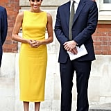 Prince Harry in a Navy Suit, and Meghan Markle in a Yellow Dress
