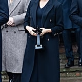 Meghan balanced darker accessories with navy blue Victoria Beckham separates on Christmas Day in 2018.