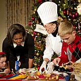 The first lady decorates cookies with children of active military personnel.