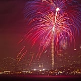 Red and purple fireworks glow over the San Francisco Bay.