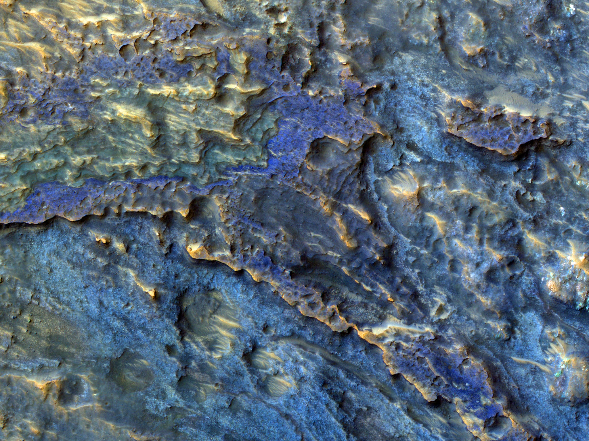 """""""This image covers part of the floor of a large ancient impact crater, near the western rim. The subimage shows layered deposits, many with distinct colors (the colors are enhanced or exaggerated). These layers have a morphology similar to that seen elsewhere on Mars in obvious alluvial fans where channels emerge into craters."""" Source: NASA/JPL/University of Arizona"""