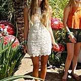 The DJ looked sweet in an ivory sleeveless lace dress, woven flats, round sunglasses, and a yellow crossbody bag at a Mulberry bash at Coachella.