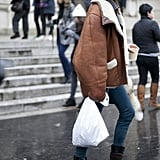 The tough-girl model uniform in full effect with an oversize suede jacket and biker boots.