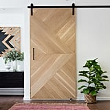 A woven pink rug sits beneath a beautifully crafted wood door that slides on a hanger.