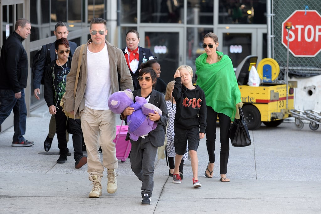 Angelina Jolie and Brad Pitt landed back in LA on Wednesday after wrapping up Angie and the kids' extended stay in Australia while she worked on her latest directorial effort, Unbroken. The group, which included all the Jolie-Pitt tots, walked to their car from LAX, with Pax, the eldest, lingering behind the group in his newly dyed red hairstyle. Earlier this week, Brad and Angie left their little ones at home to attend the wrap party for Unbroken. In fact, Brad was still wearing the same army boots that he wore to Angie's party when he arrived back in California. Meanwhile, Angelina, who normally wears all black, decided to brighten up her outfit with a green scarf. Now that the Jolie-Pitts are back in their home base of LA, they may soon start planning Brad's trip to the Oscars in March. Brad's film 12 Years a Slave is nominated for best picture, among many other awards. Back in November, the couple brought Maddox on the red carpet when Angelina accepted an honorary Oscar for her philanthropic work, so maybe we'll see one of the other Jolie-Pitt kids take a spin down the carpet come March.