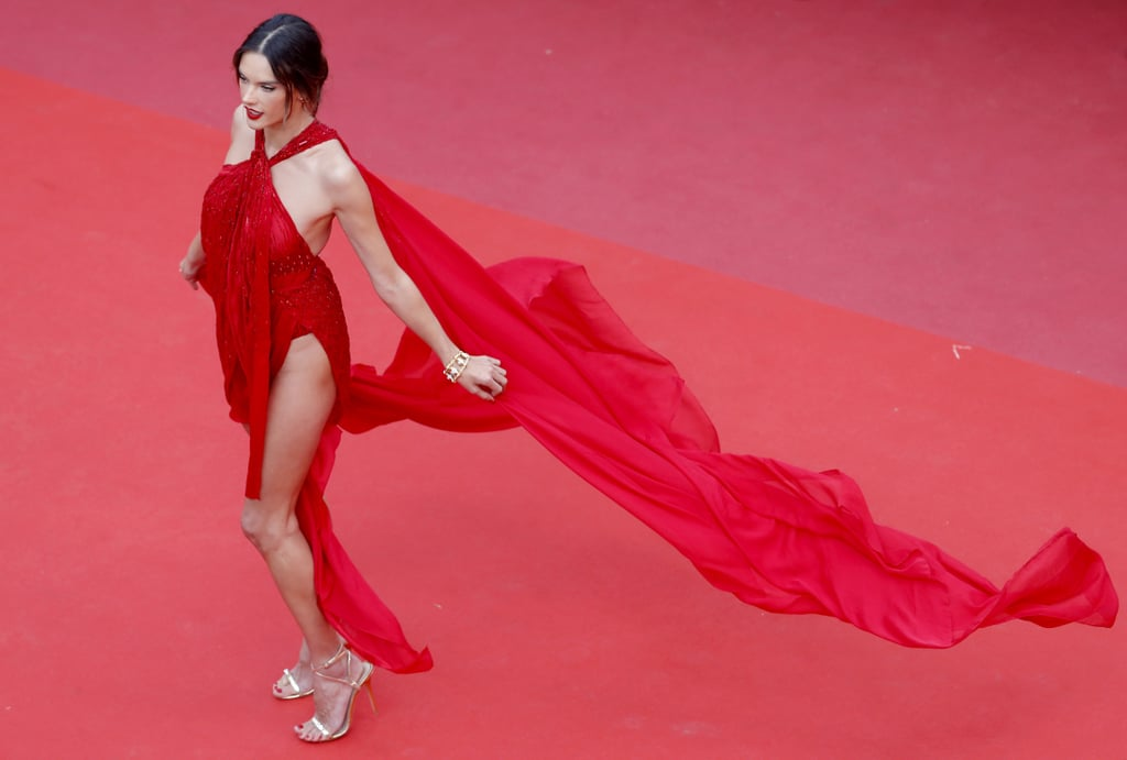 Alessandra Ambrosio basically staged her own one-woman runway at the Cannes Film Festival. Attending the premiere of Les Misérables on May 15, the model wore a dramatic Julien Macdonald gown featuring a lot of eye-catching elements with its halter neckline, silk chiffon cape, and high leg-baring slit. Alessandra completed her look with a pair of gold strappy Giuseppe Zanotti sandals, red teardrop earrings, gold rings, and a tassel bracelet.  The complete look ended up being one of her sexiest to date — and that's saying a lot, considering she used to be a freaking Victoria's Secret Angel. Alessandra was clearly feeling it, too, as she twirled and flung her cape all along the red carpet. See photos of the memorable Cannes fashion moment ahead.       Related:                                                                                                           Selena Gomez Knows That Cannes Is Much More Fun in Leather and Diamonds