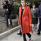 While visiting a children's hospital in February 2016, Queen Letizia paired her all-black outfit with two statement jackets — a sparkly cropped number with a fiery red Hugo Boss trench over the top.