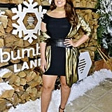 Ashley Graham wearing a belted dress with a metallic shawl at the Winter Bumbleland.