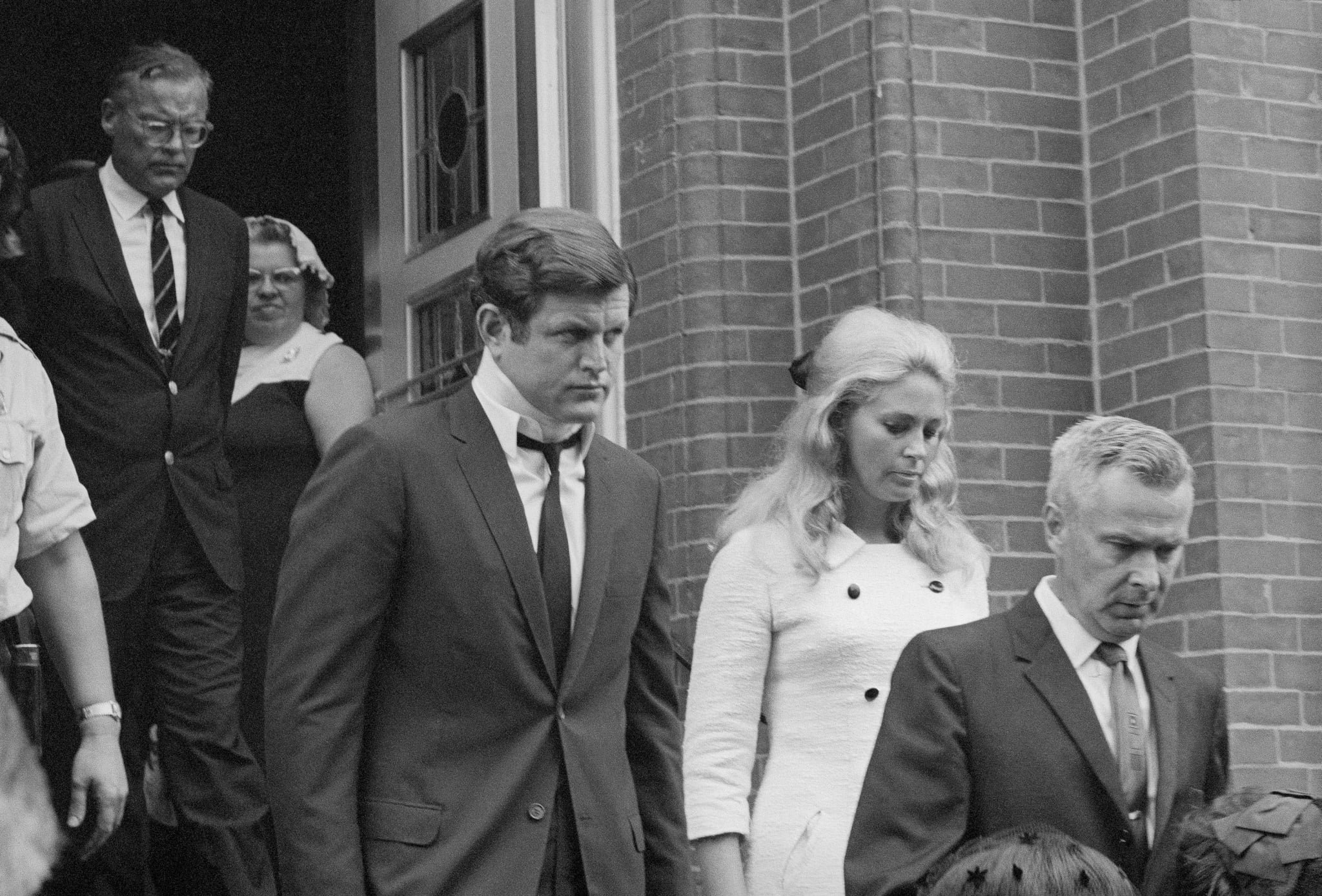 (Original Caption) Plymouth, PA: Sen. Edward Kennedy leaves St. Vincent's Church with his wife, Joan after attending the funeral Mass celebrated for Mary Jo Kopechne, who was killed in an auto crash with the Senator. Mary Kopechne was on the secretarial staff of the late Sen. Robert Kennedy.