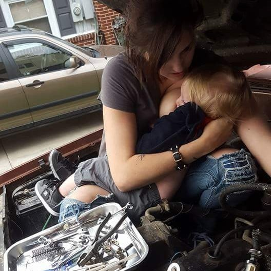 Mom Breastfeeding While Fixing Truck Engine
