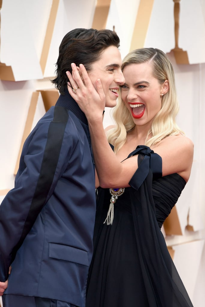 Being hollered at by photographers to smile and face in certain directions on the red carpet can only be alleviated by one thing, and that's Timothée Chalamet's charm. During Sunday night's Oscars, Margot Robbie gave the cameras her most striking poses when she was suddenly surprised by Timothée himself. That's right, the Little Women actor popped up from behind and photobombed Margot and it's the one of the greatest red carpet interactions we've seen yet. Check out their adorable exchange in front of the cameras ahead, and see photos of Margot and Timothée at the Oscars.