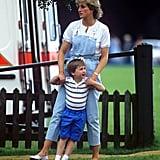 """الأميرة ديانا مع الأمير ويليام في مباراة """"بولو"""" ارتدت فيها أفرول دينم باللّون الأزرق الفاتح مزوّدٍ بحزامي كتف بيضاوين، وقرنته بقميص أبيض ذو أزرار مع حذاء """"لوفر""""."""