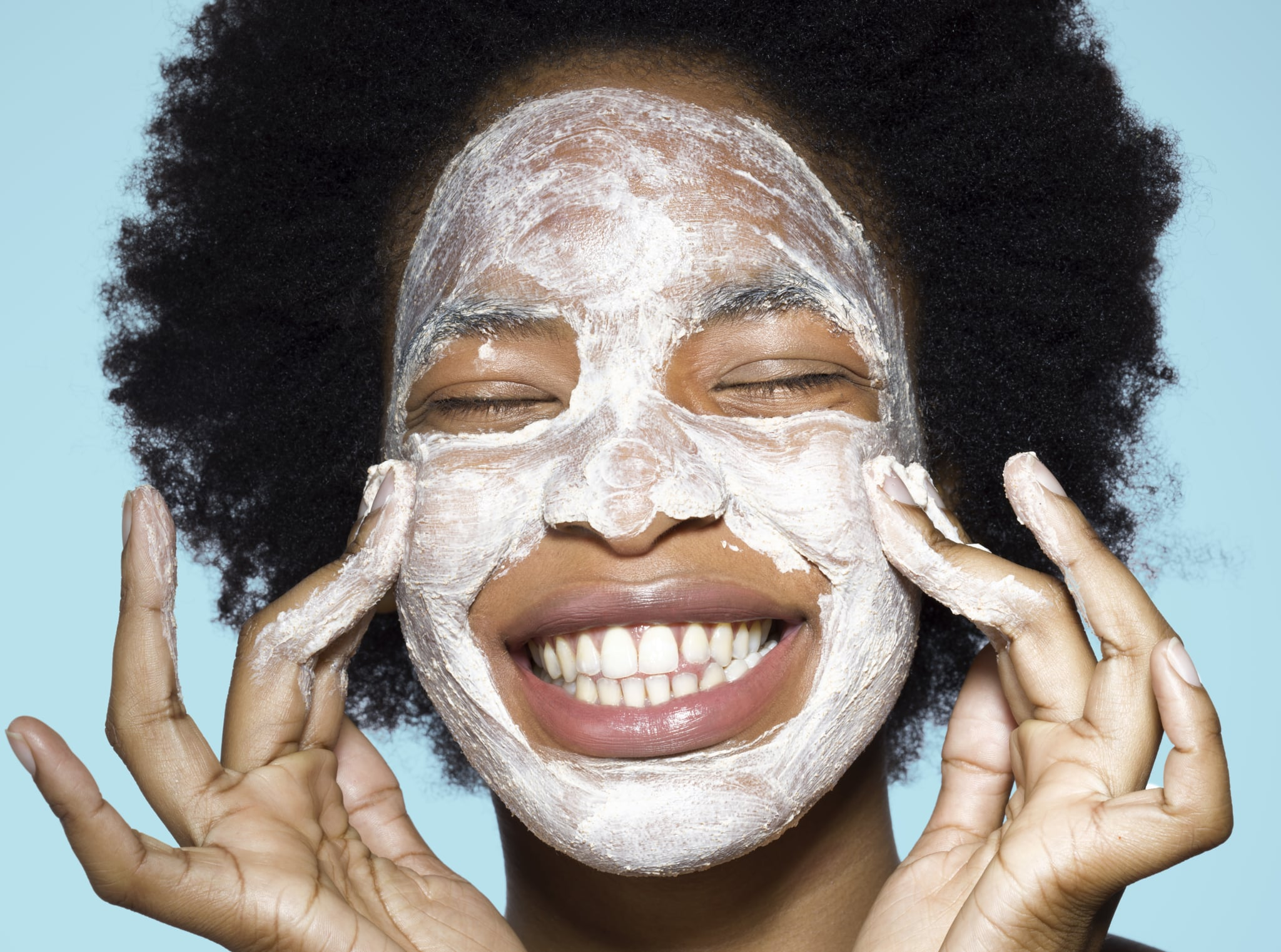 Close-up of young mixed-race woman applying white face cream face, face mask, with turquoise background