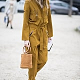 Give Your Boiler Suit a Feminine Look With White Heels and a Bucket Bag