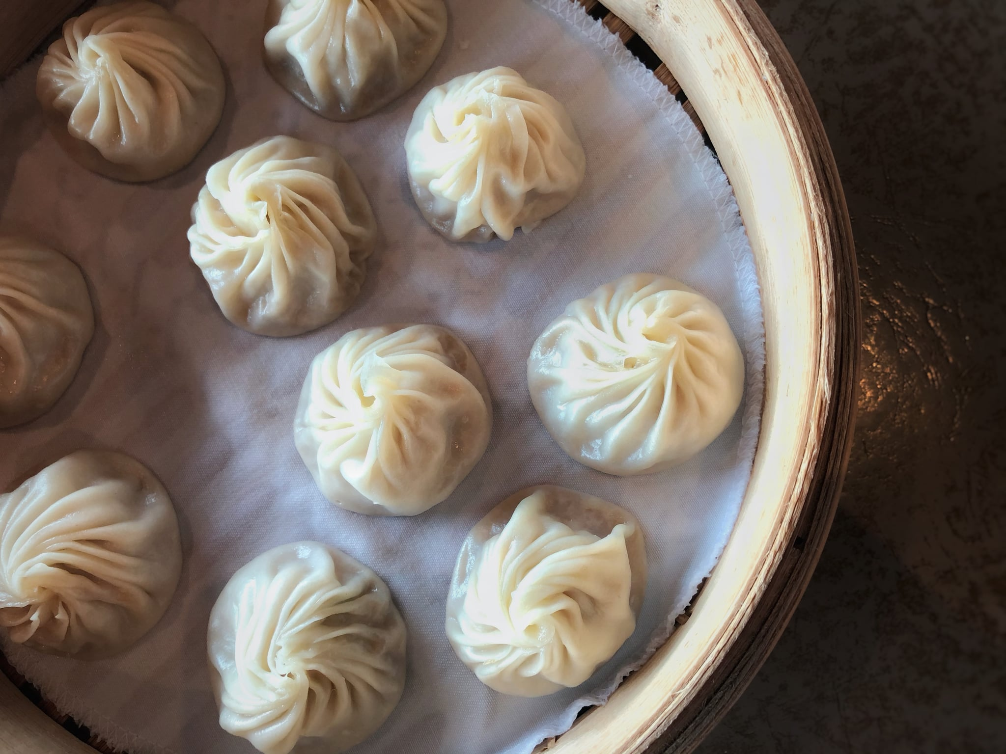 An overhead view of a basket of Chinese steam soup dumpling also known as Xiao Long Bao - 小笼包