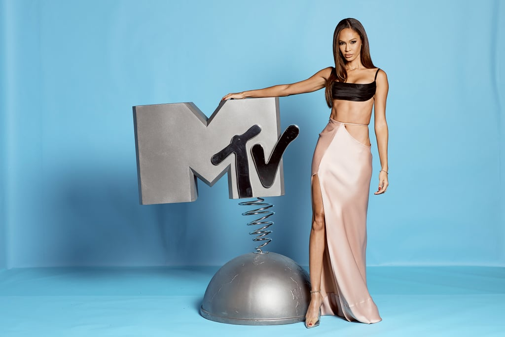 We have reason to believe that Joan Smalls is a time-traveler. For the 2019 MTV Europe Music Awards in Seville, Spain, on Sunday, the model wore an outfit seemingly plucked out of the '90s, one that we could easily imagine being worn by Kate Moss, Naomi Campbell, and other greats from that decade.  But alas, Joan's satin separates are actually from Brandon Maxwell's Spring 2020 collection. The strappy bra top is actually the same one Dakota Johnson wore to the recent Governors Awards, although she paired hers with a big ballgown skirt. Joan, meanwhile, contrasted her black top with a pink slip skirt featuring a thigh-high slit. She completed the look with pointed-toe stilettos by Jessica Rich. See pictures of Joan in the sexy separates with a throwback feel ahead.      Related:                                                                                                           Not Many People Can Pull Off This Sexy Mugler Bodysuit, but Dua Lipa Sure Can