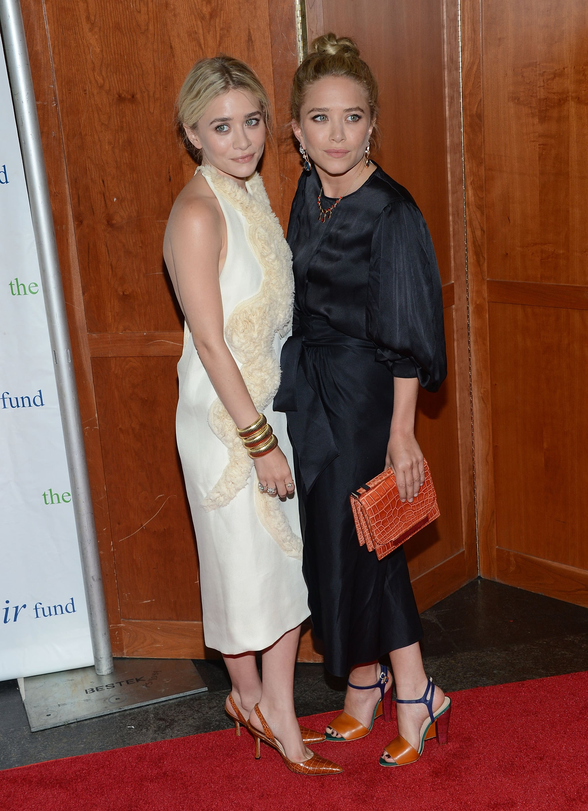 Twinning combo: For the Fresh Air Fund's Salute to American Heroes event in July 2012, the twins coordinated their cocktail-chic ensembles, both by The Row, by choosing sleek hues at opposite ends of the color spectrum.  Ashley looked angelic in a fitted and textured white halter dress, which she accessorized with sling-back pointed-toe pumps and stacks of gold bangles. Mary-Kate stepped out in a kimono-style black sheath, complete with a sash at the waist, and colorblock sandals.