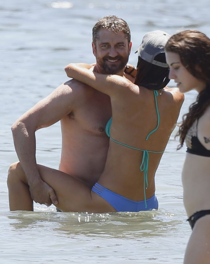 Gerard Butler showed off a lot more than his sexy smile in Malibu, CA, on Saturday. The actor showered his bikini-clad girlfriend, Morgan Brown, with PDA during the duo's beach day. At one point, Gerard's muscles bulged up as he held Morgan in the water. They also scored some exercise, working their physiques — just look at those abs! — while paddleboarding. The Scottish actor last gave us a glimpse of his connection with Morgan when the couple got physical in the water last September. Read on to see their latest snaps, and then scroll through the hottest celebrity beach PDA pictures.
