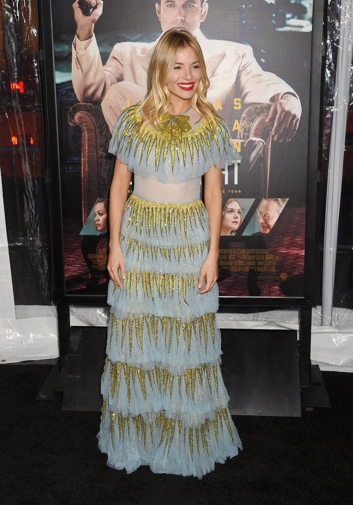 If living by night will make us look half as good as Sienna Miller did at the Live by Night premiere on Tuesday, then we're cancelling our schedules and sleeping in the day from now on. The British actress, model, and beauty chameleon looked a dream in a tiered, baby blue Gucci dress paired with a bold, red lip as she posed alongside co-stars Elle Fanning and Zoe Saldana. Sienna plays Emma Gould, a feisty flapper from Boston tied up with Irish gangster Albert White (played by Hustle's Robert Glenister) in the film. Read on to see Sienna's look from all angles before the film hits cinemas on 26 January.