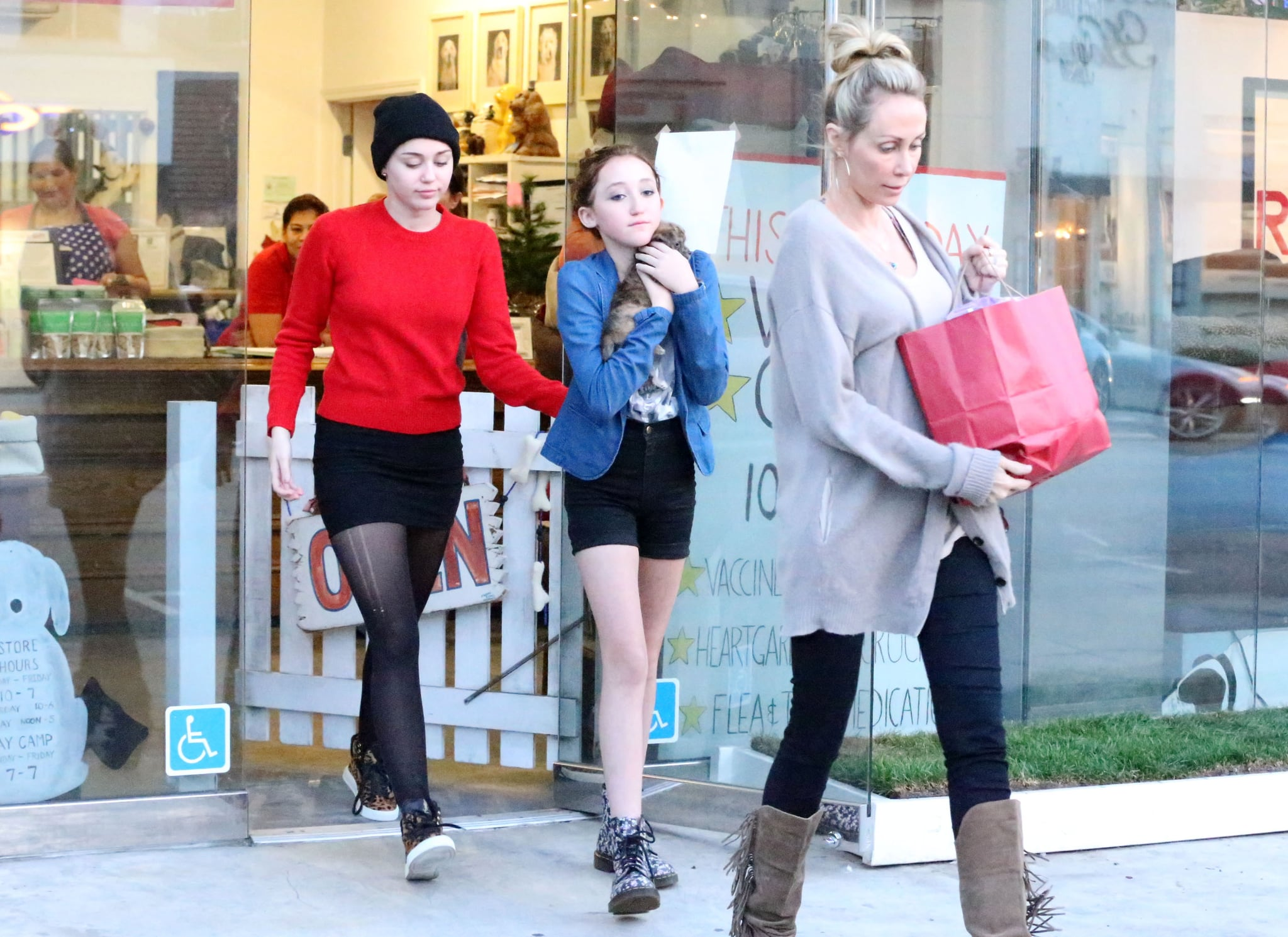 Miley Cyrus and her sister carried a puppy out of a pet store.