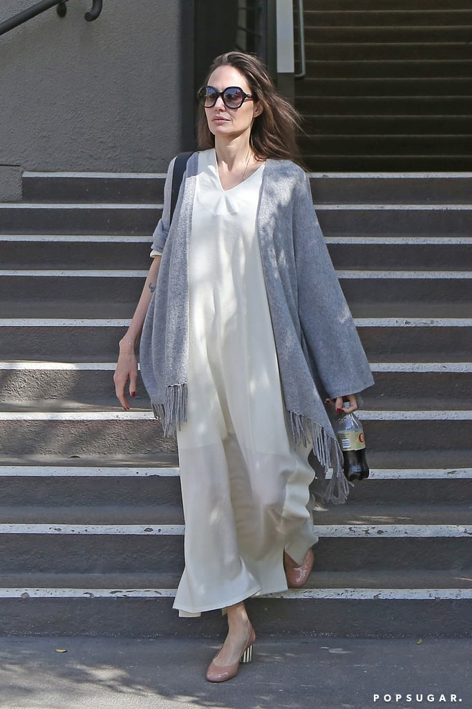 "Angelina Jolie's the type of street style star to toss a shawl over a dress and cause every onlooker to muse, ""Wow, she looks amazing."" It's that effortless approach to fashion that has all of us scrambling to re-create her outfits. By now, we've got her style preferences narrowed down — simple, neutral pieces — so when she stepped out in a Summer-like ensemble, it just looked like an ""Angelina outfit"" rather than something seasonal. The star rocked a cream-colored sheath dress with a go-to pair of pink Salvatore Ferragamo block heels. To continue with the neutral theme, Angelina draped a gray Gerard Darel poncho over the dress and sported a pair of oversize shades. Angelina's outfit was made of, basically, three easy pieces, and it's a look we can all replicate. Start building your own Angelina-inspired wardrobe with similar dress selections ahead.      Related:                                                                                                           14 Lessons in Power Dressing Straight From Angelina Jolie"