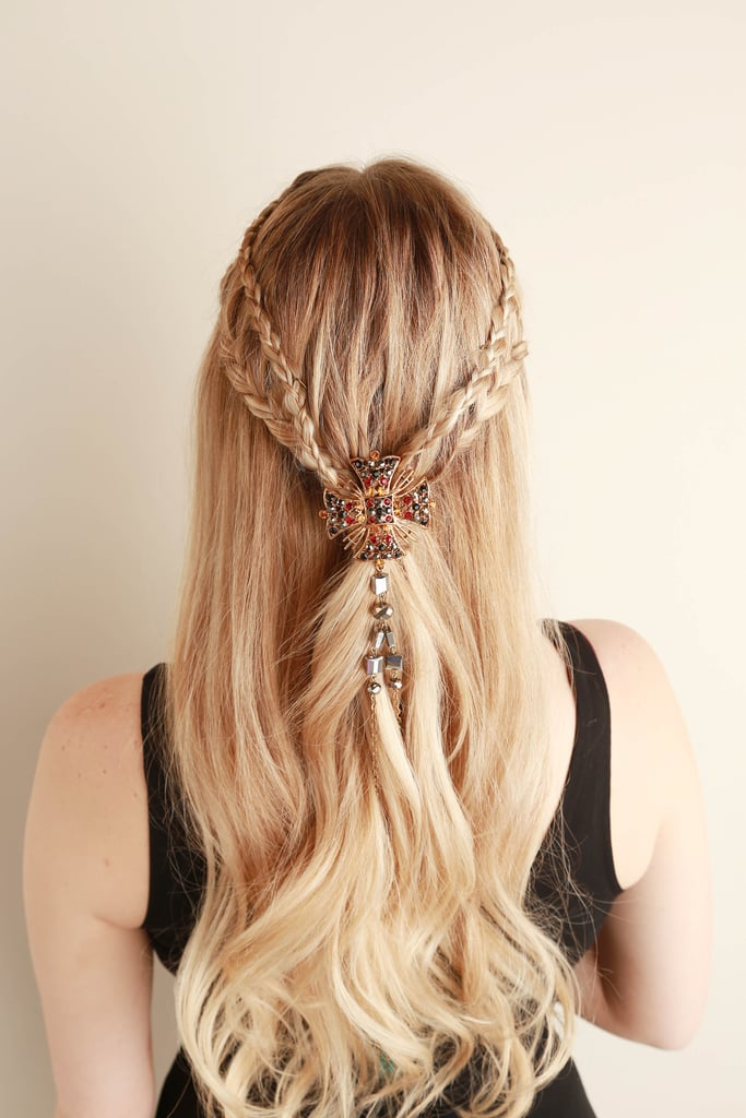 Take a large jeweled ring, bracelet, or necklace (the latter was used here) and secure it into the hair. Adding jewelry makes the look very Game of Thrones-inspired. And it covers up where your braids meet in the back.