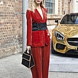 A red suit is already an extraordinary outfit, but a corset belt added even more drama in just the right way.