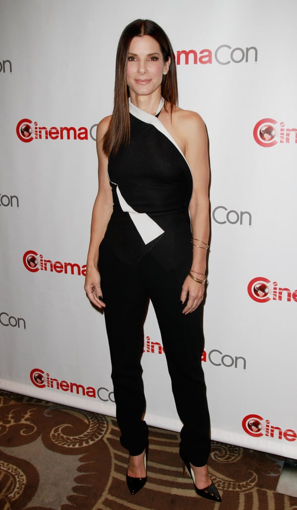Sandra Bullock made a very chic appearance at CinemaCon in Las Vegas wearing a black and white one-shouldered jumpsuit and black Rupert Sanderson patent pumps.