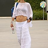 For a July 2012 beach day, Gwen went monochrome, sporting a sheer white dolman-sleeve tee and white ruffled maxi skirt. She topped her crisp duo with a straw fedora, hot-pink Quay Eyewear sunglasses, and statement bracelets.